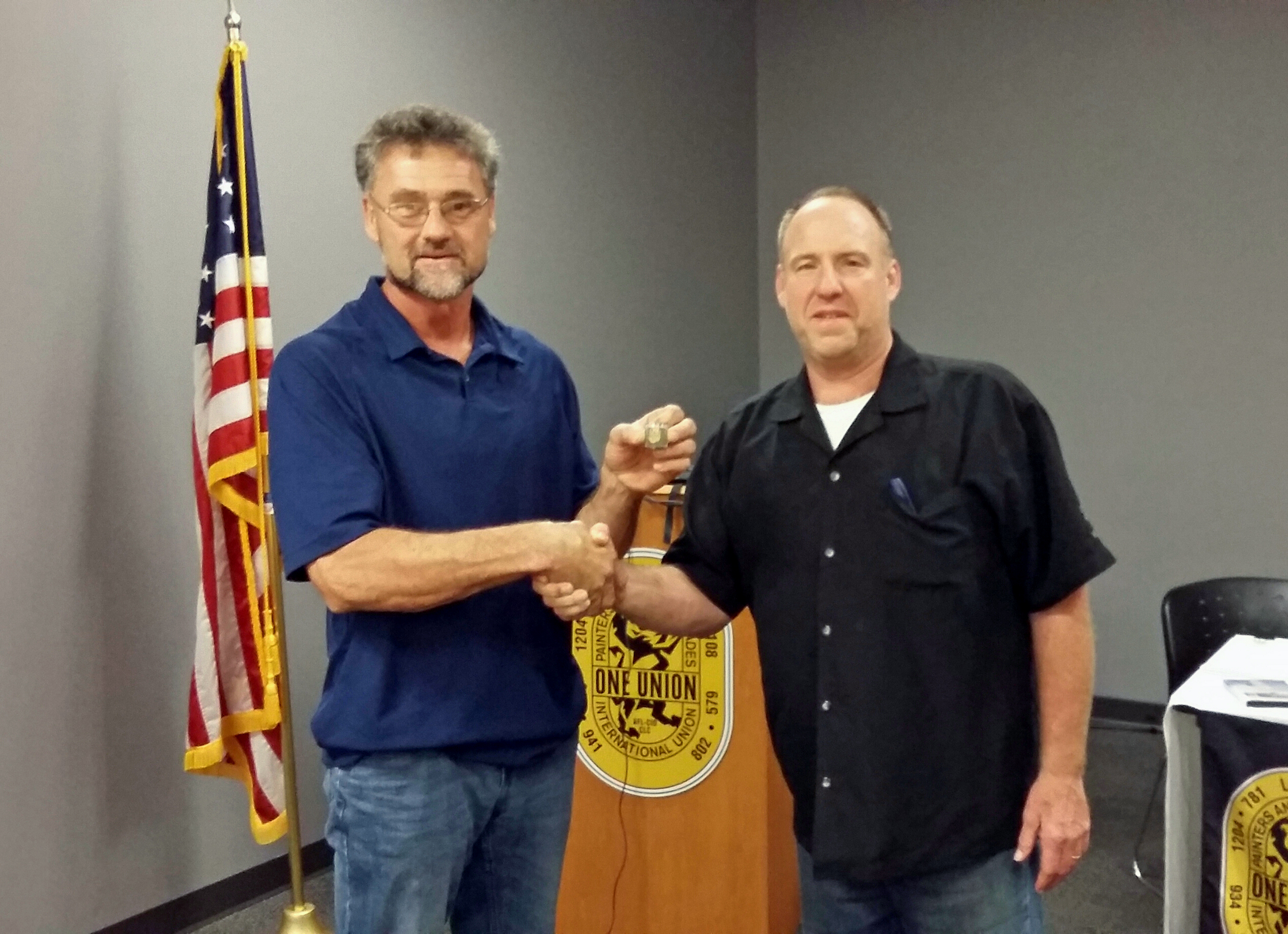 Local Union 781's Curt Belden accepts his 30-year service pin during a monthly meeting.